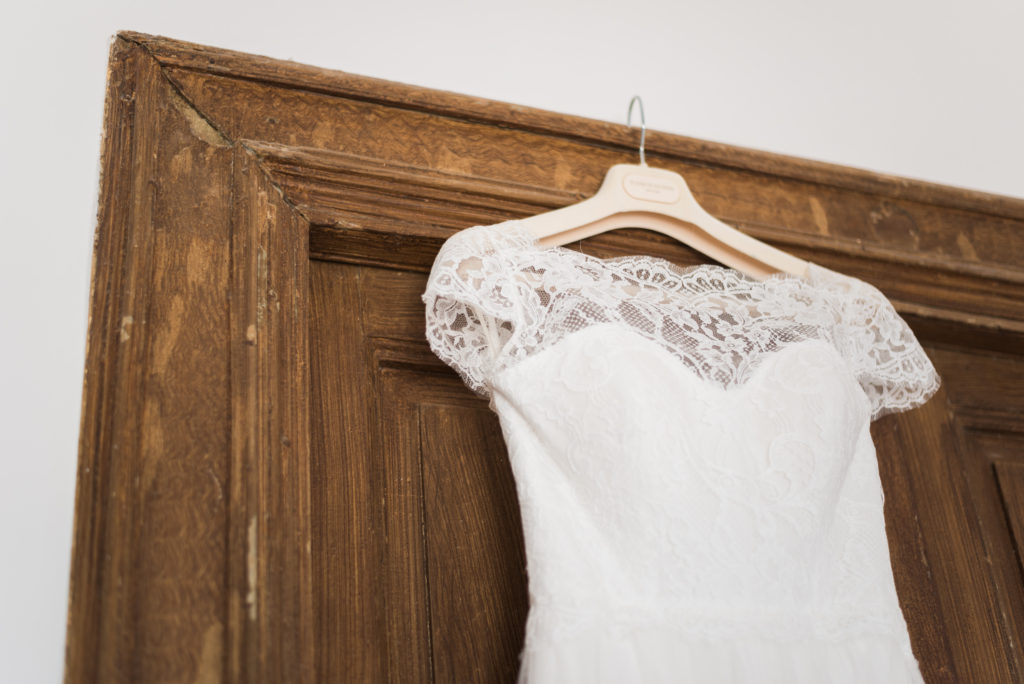 lace wedding dress hanging on door